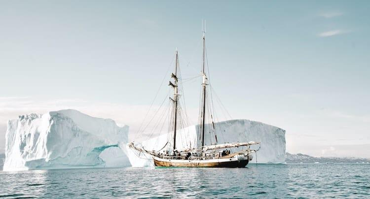 An old wooden boat sitting in front of an Iceberg