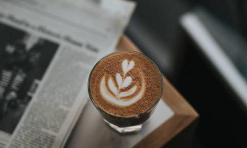 A coffee cup sat beside a newspaper