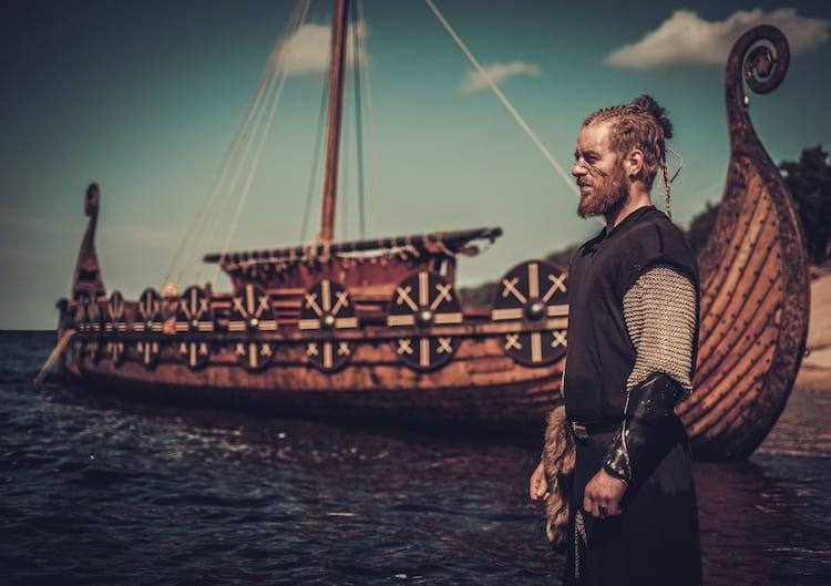 A Viking warrior with sword standing in front of a wooden Viking longboat