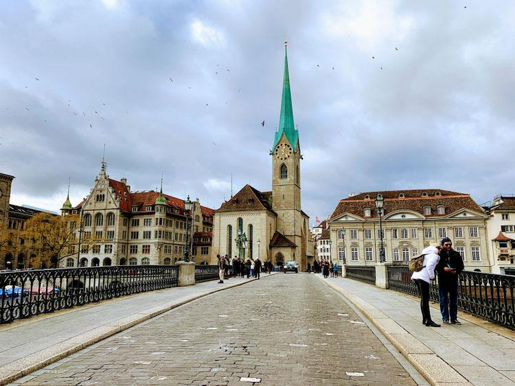 A bridge in Zurich. Cobbles down the middle, black railings either side and a striking church in the centre with a turquoise pointed roof