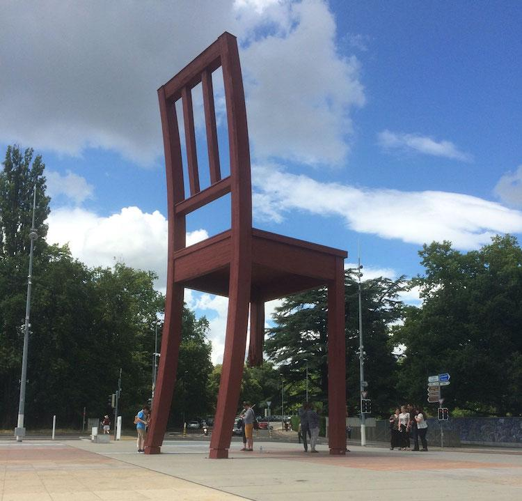 A huge red chair with one leg broken