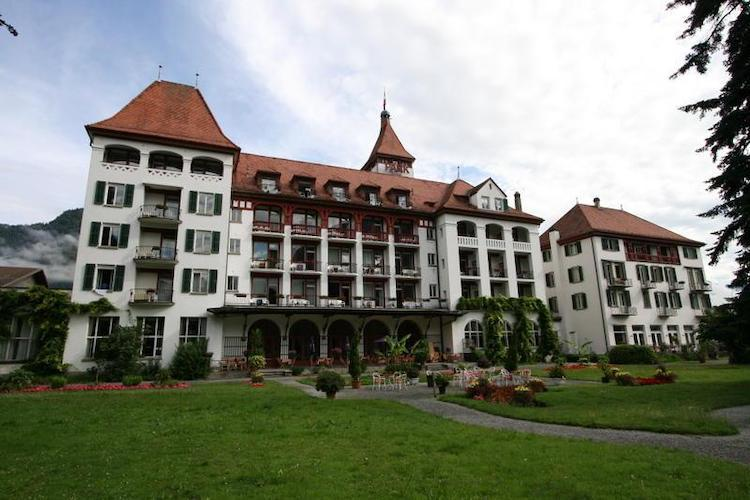 A big white building with many many windows and a red roof