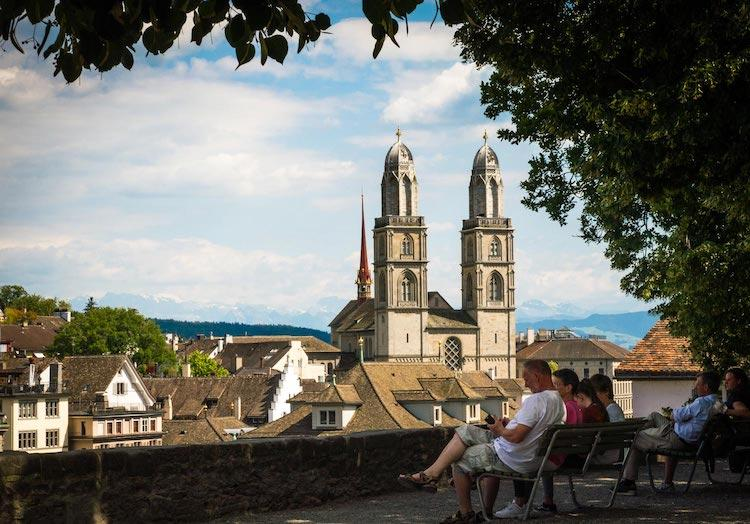 A view of Grossmunster in Zurich. 3 people are sitting on a bench looking at the Cathedral with it's two rounded tower