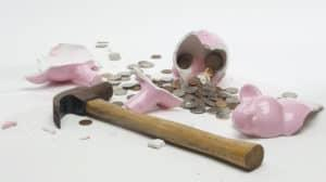 A hammer lying beside a smashed pink piggy bank full of coins