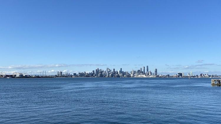 Melbourne CBD with water in front and blue skies to the back