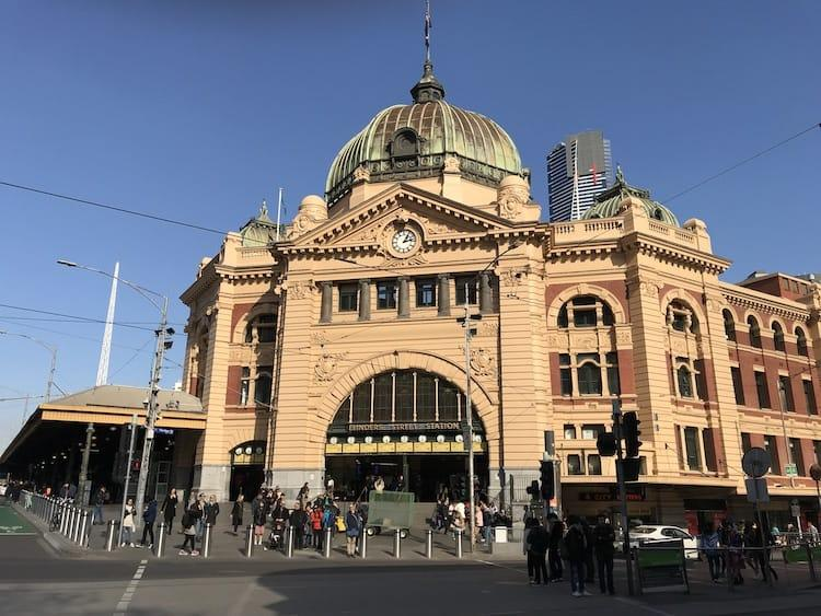 Flinders Street Station. A big yellow building, with archway above the entrance which has multiple clocks above it.
