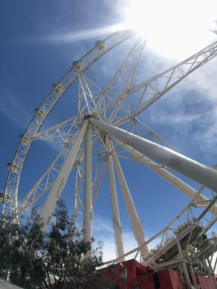 A large, white Ferris wheel with blue sky behind it