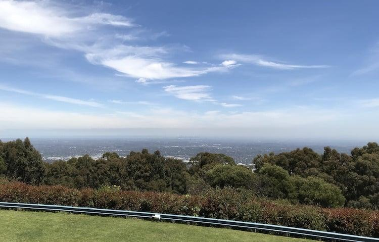 A view of Melbourne from the top of a mountain. It is a long way off in the distance, the sky is bright blue