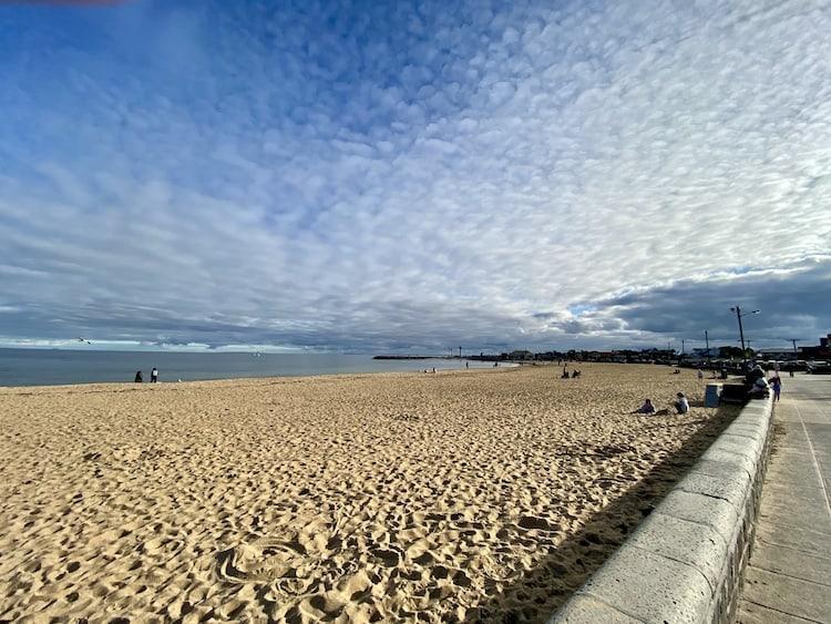 Photo of a sandy beach with a dappled white cloud agains a beautiful blue sky