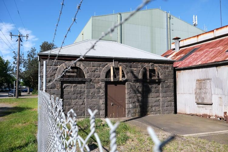 Side view of Williamstown Morgue a bluestone building surrounded by barbed wire