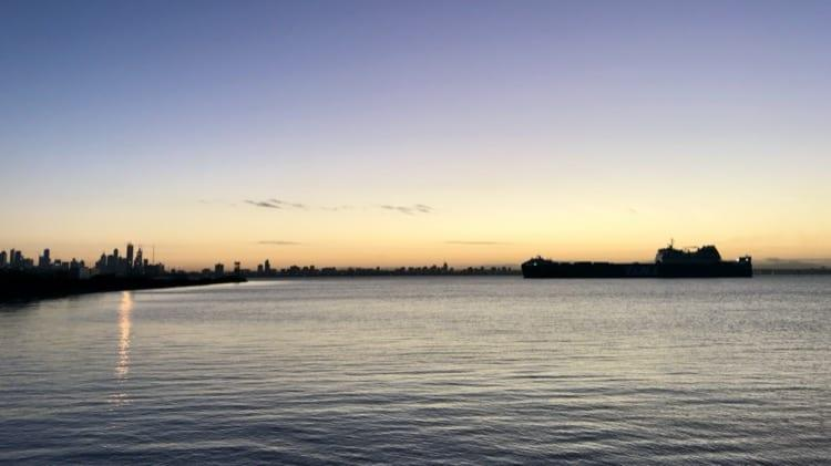 Sunset of a large boat with Melbourne city behind it