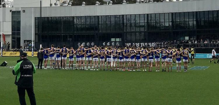 AFL players from Williamstown seagulls line up facing away from the camera with arms over each other's shoulders singing an anthem