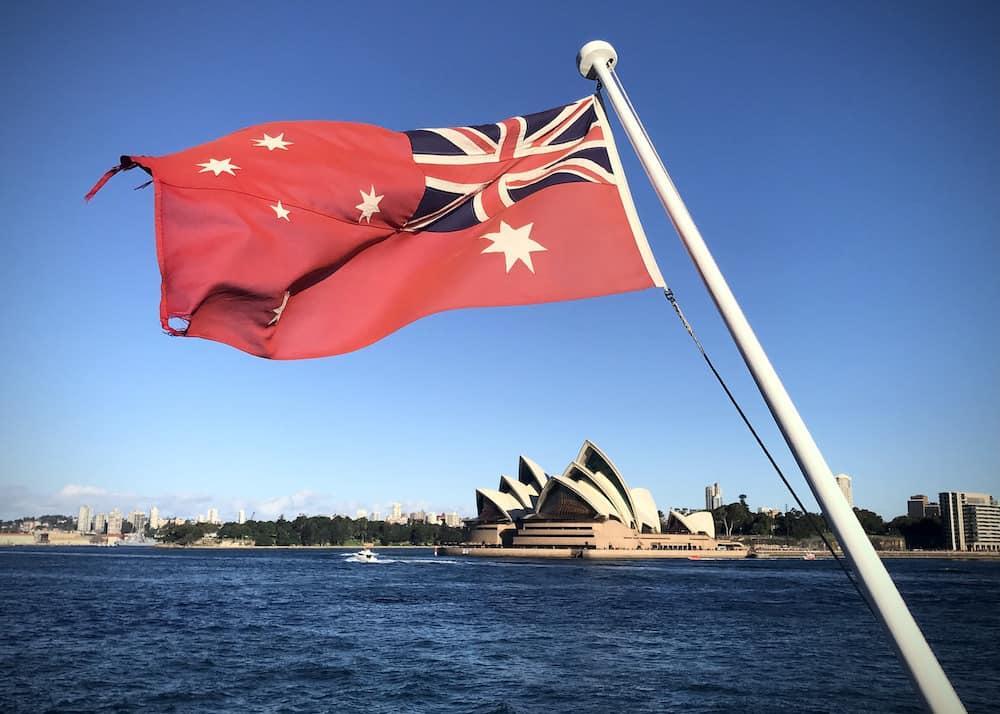 sydney opera house with red australian maritime flag