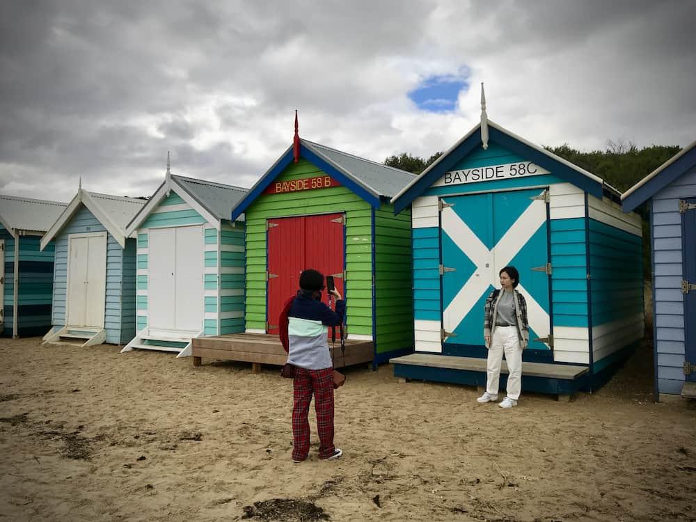 tourist getting photo at brighton beach boxes